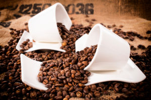 Row coffee beans splashed from the cups